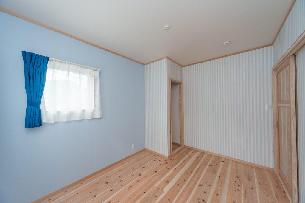 水色の無地とストライプの壁と無垢材が相性◎カーテンの青もきいています