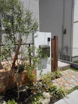 木の柱、白い漆喰壁にグリーンのポストや緑がはえる門柱