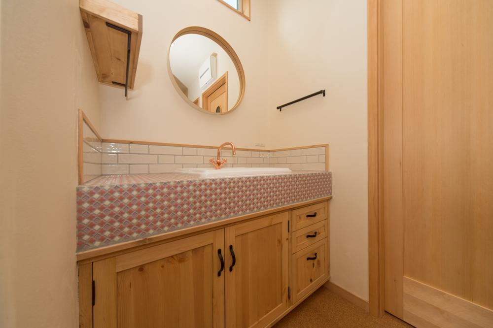 丸い鏡とこだわりタイルの造作洗面カウンター