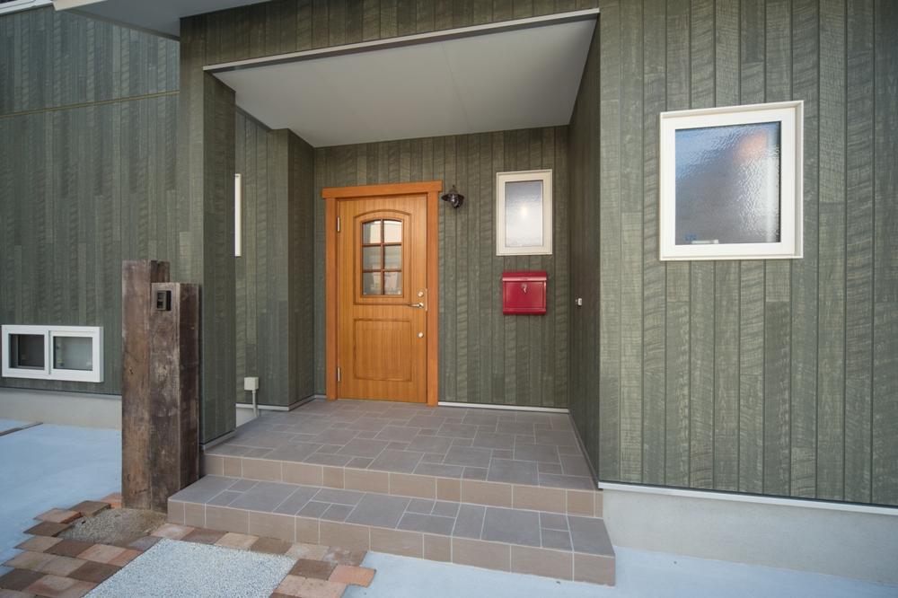 ノースグリーンの外壁に白いサッシや茶系の外構、そして赤いポストがアクセント