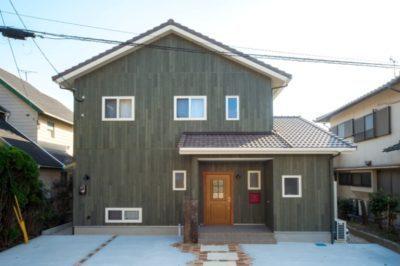 ノースグリーンの外壁に白いサッシ、チョコレート色の屋根、そして赤いポストとチークの玄関ドアがアクセント