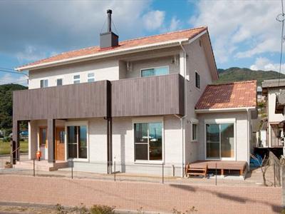 オレンジ色の屋根から茶色の煙突、白い壁にバルコニーは木貼のコントラストがステキな外観