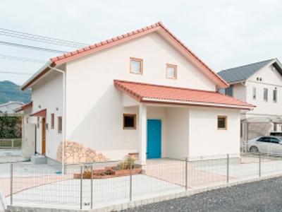 白い壁にオレンジ色の屋根、鮮やかなブルーの玄関ドア
