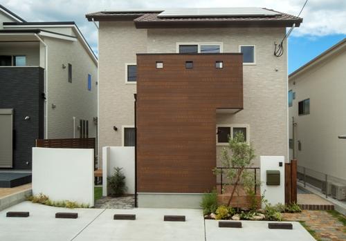 茶系の外観と白い漆喰壁や植栽のコントラストが美しい家