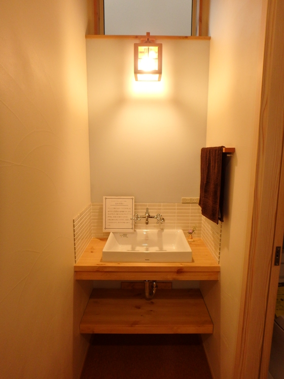 白いタイルと淡いブルーの漆喰壁がアクセントの手洗いカウンター