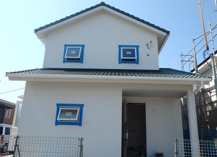 緑の瓦と青の窓モールがアクセントの家