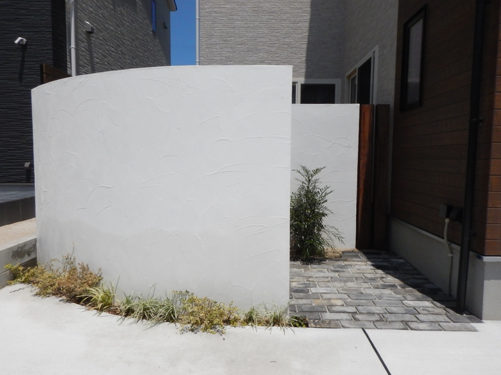 アールの白い壁に木の柱、シックなタイル、植栽がステキな外構