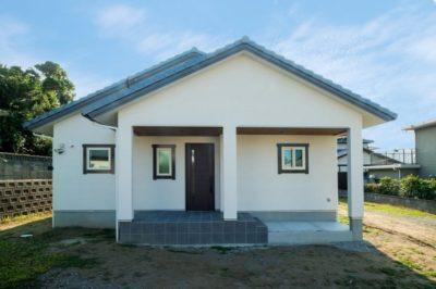 白い壁にブルーグレーのタイル・洋瓦、茶色の建具や天井がアクセントの家