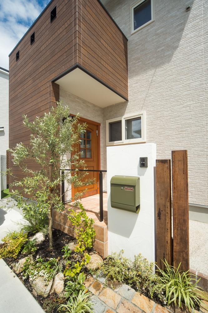 木の柱、白い壁にグリーンのポストや緑がはえる門柱