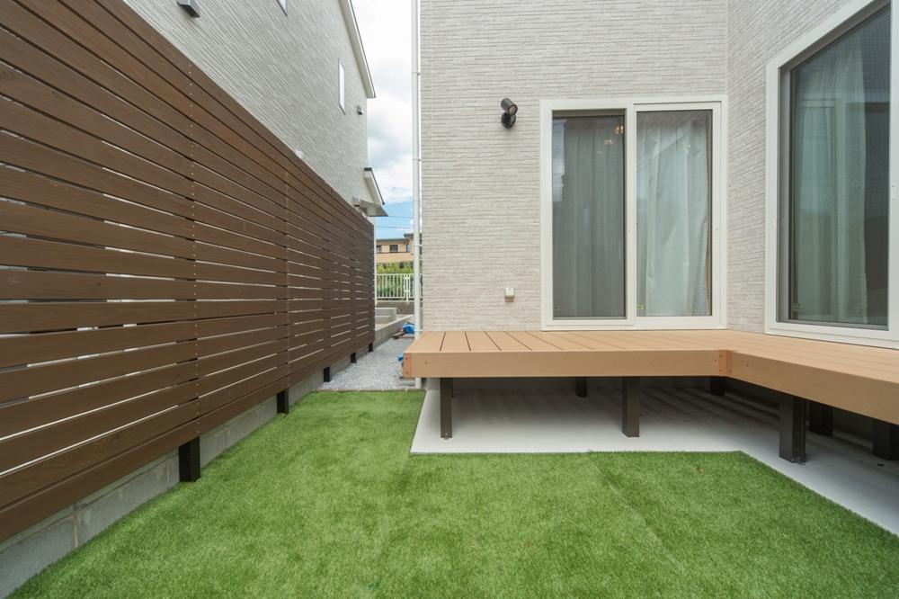 木製デッキと芝生のコントラストが美しいお庭
