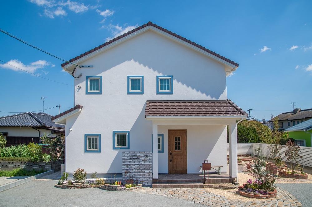 漆喰の白にブルーグレーの窓枠、チョコレート色の屋根、大人のかわいさが光る外観